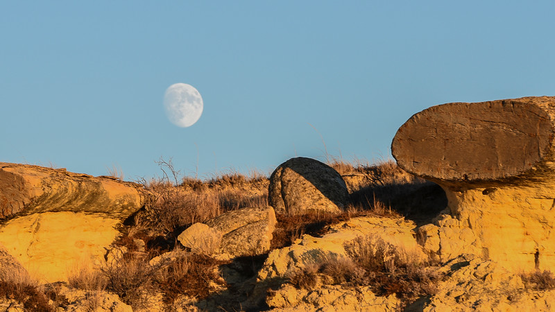 Full moon over badlands rocks