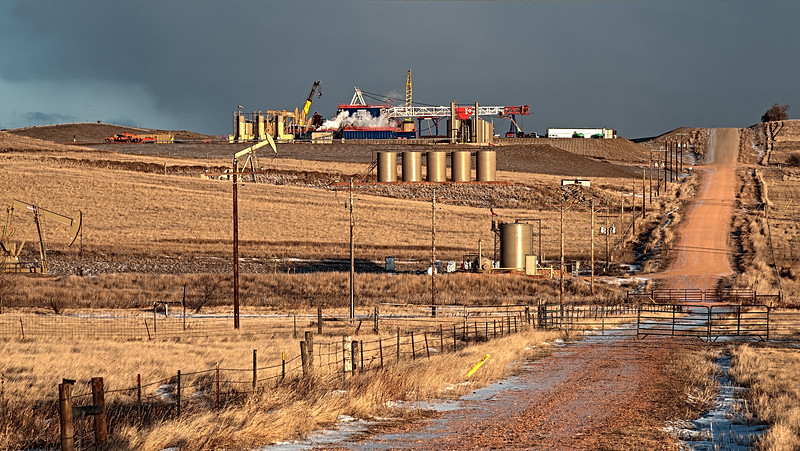 West of Watford City, the evening sun behind the camera illuminates the pre-set drilling rig for a new oil well.  Below the hill are two other pump pads indicating this is a place where oil-rich shale is in abundance.