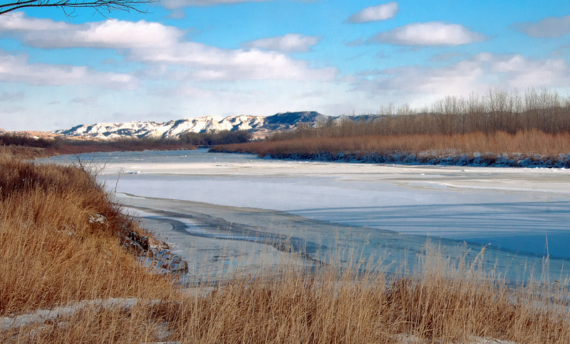 The first open water next to the shore of the Little Missouri River indicates spring is not far.  Still, the snow on the far away bluffs also show that winter isn't far gone, either.