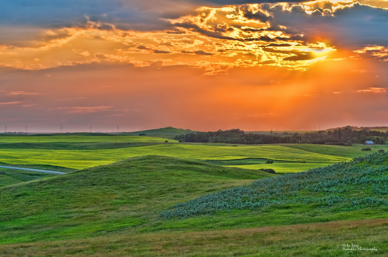 The prairie tapestry in spring is variant shades of green. The rolling hills of northeast Burleigh County display the tapestry.  A hazy, smoke-colored sunset (from Canadian forest fires) adds a warmth to the scene.  The Baldwin and Wilton wind farms can be seen on the horizon.