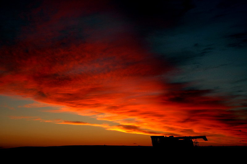 Coming home to where I lived at the time, in a hunting lodge in the Knife River Valley near New Town, I watched the sunset become more intense.  I walked out in to a flax filed to get the silhouettte of the parked combine.