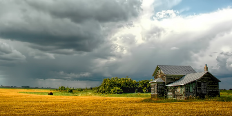 "Late summer day,  a few years ago, I waited along the highway for the migrating sunlight to pass by the abandoned farm and glowing stubble field. A heavy rain shower immediately washed out the scene forever.<br /> <br /> You can own this image as a print, a canvas wrap or even a coffee cup or mouse pad.  Just click the ""buy"" button to browse the options."