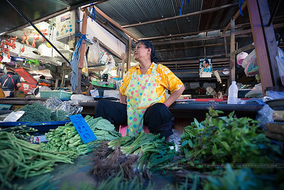 La vendeuse, ses légumes et, plus loin, la photo du roi.