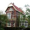 BP030  Hoofdstraat 78 - villa De Tijloos<br /> <br /> Dit pand uit 1902 bestaat uit drie delen; één deel van drie verdiepingen, aan de linkerkant een gedeelte van twee verdiepingen en een serre met balkon aan de rechterzijde. Het pand is opgetrokken met rode bakstenen die in kruisverband zijn gemetseld. Grijze speksteenbanden van pleisterwerk lopen over het hele huis. <br /> <br /> Meer informatie is te vinden in 'Monumenten in Sassenheim', een uitgave van de Stichting Oud Sassenheim.