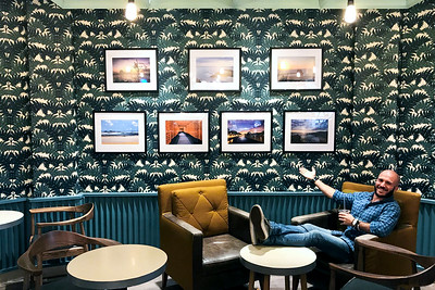 Aaron Northcott Sitting with his Framed Prints Hanging on the Cafe Wall