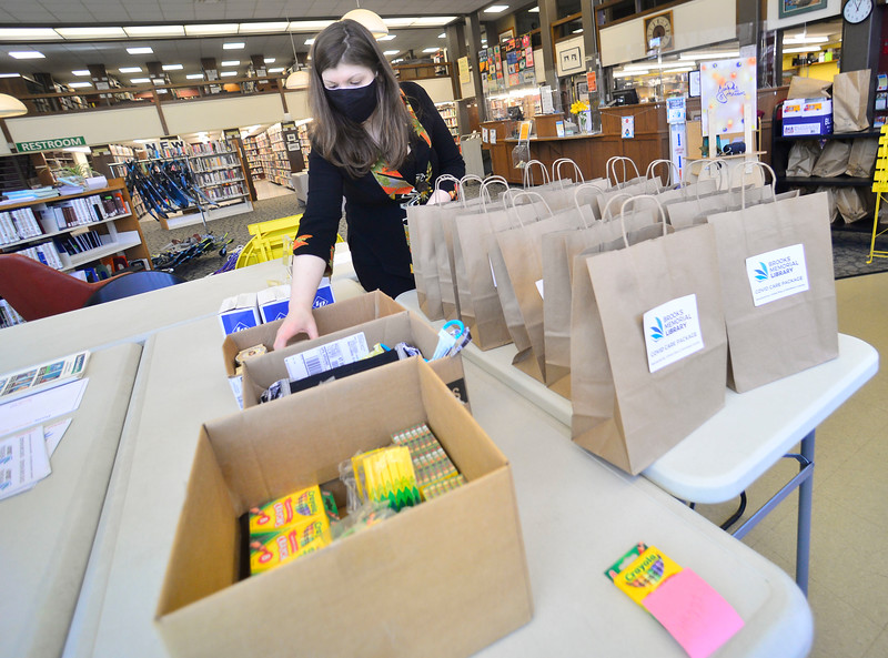 Courtney Carey, the circulation manager for the Brooks Memorial Library, in Brattleboro, Vt., fills COVID Care Packages with masks, lotions, and crayons, as part of an effort sponsored by local organization.