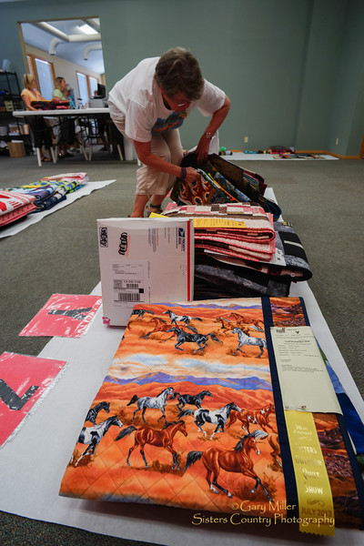 Liz Weeks retrieving an owner's quilt. Monday July 15th in Sisters, Oregon, following the wrap-up of the Sisters Outdoor Quilt Show weekend, finds volunteers still hard at work with the monumental task of returning -- by hand or by by post -- to the proper owners all of the 1,400 quilts that participate in the largest outdoor quilt show in the world. Image taken as part of Project Dayshoot+30, #dayshoot30, for the Oregon Historical Society - Copyright © 2013 Gary N. Miller, Sisters Country Photography