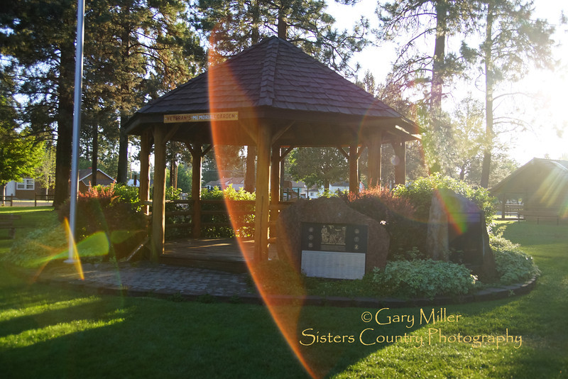 The first rays of sun light up the gazebo and veterans memorials at the Village Green Park in Sisters, Oregon on July 15, 2013. Image taken as part of Project Dayshoot+30, #dayshoot30, for the Oregon Historical Society - Copyright © 2013 Gary N. Miller, Sisters Country Photography
