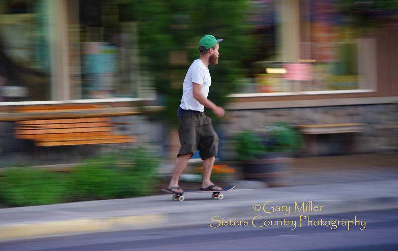 A skateboarder whizzes down the sidewalk of Cascade Street in Sisters, Oregon after a dusk recharge of frozen yogurt at the Cuppa Yo shop. Image taken as part of Project Dayshoot+30, #dayshoot30, for the Oregon Historical Society - Copyright © 2013 Gary N. Miller, Sisters Country Photography