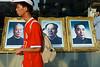Un homme passant devant les portraits de grandes figures du parti communiste chinois (dont Mao) exposés dans la vitrine d'un photographe de la rue Wangfujing à Pékin. Beijing/Chine