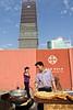 Petit cuisinier de rue installé devant le mur d'enceinte d'un chantier du nouveau quartier de Soho à Pékin. Beijing/Chine