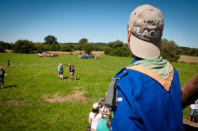 Woodscout - Dans la plaine, sous le soleil belge, un scout guide ses congénères pour un jeu de repérage dans l'espace