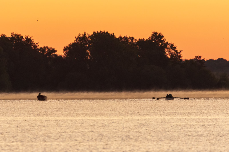 Safety boat and four person rowing boat set out on the Bay of Quinte.