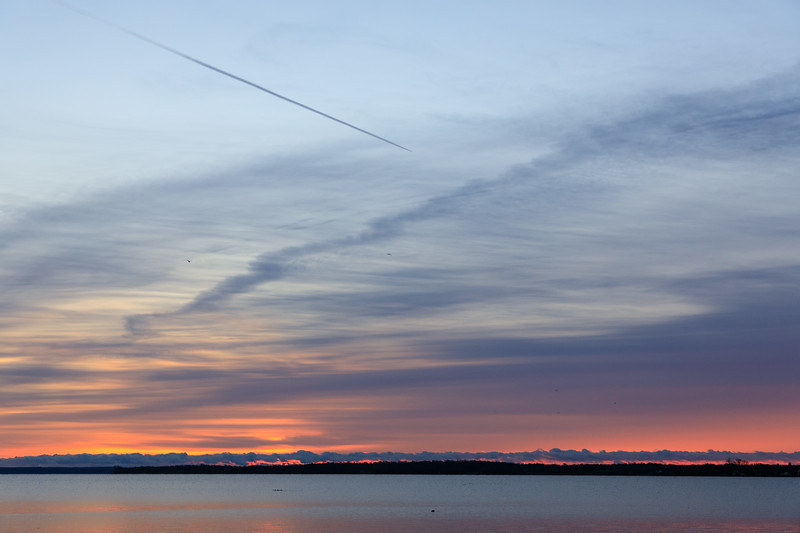 Sky and contrail over the Bay of Quinte before sunrise.