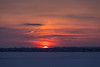 Edge of the rising sun visible across the Bay of Quinte.