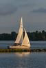 A sailboat passing along the breakwater