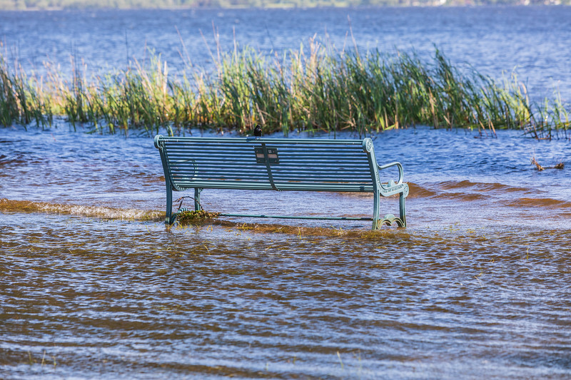 Park bench in the water. Waves.