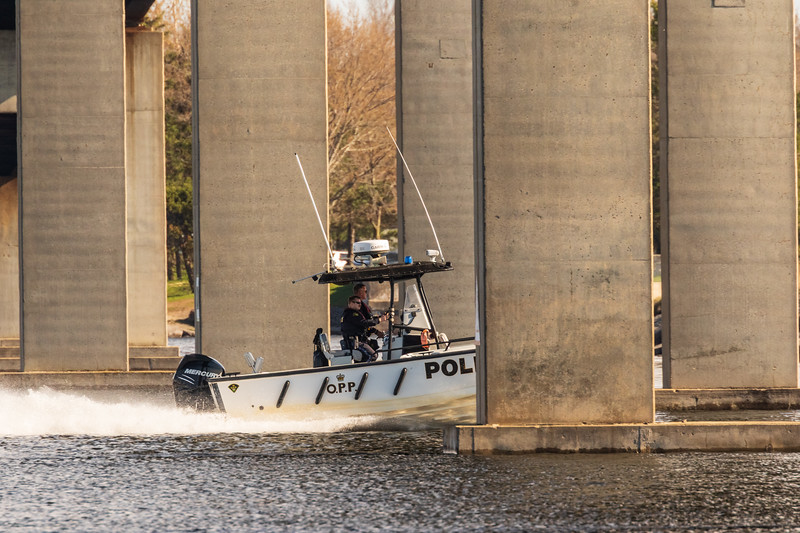 Ontario Provincial Police boat heads under the Norris Whitney bridge on the Bay of Quinte at Belleville Ontario 2019 May 5. White balance off hull.