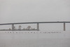 Cormorants flying low over the Bay of Quinte in front of the Norris Whitney Bridge on a cloudy morning.