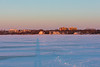 North shore of the Bay of Quinte at sunrise: Belleville General Hospital, Pier 21, Bay Terrace Apartments, Quinte Rowing Club, Herchimer Boat Launch. Shadow of photographer on the ice.