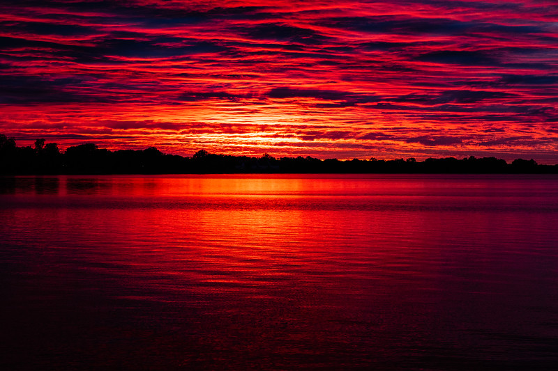 Purple sky reflected in the water of the Bay of Quinte before sunrise at Belleville Ontario 2020 May 31.