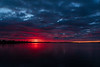 Wide view of purple sky reflected in the water of the Bay of Quinte before sunrise at Belleville Ontario 2020 May 31.
