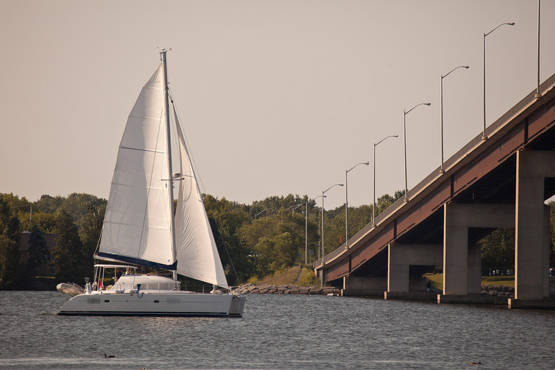 Sailboat passing under Bay Bridge