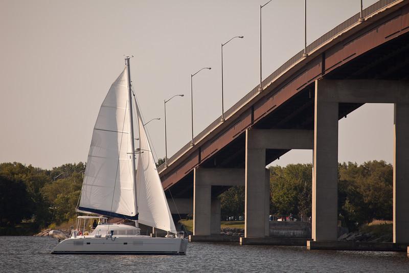 Sailboat passing under Bay Bridge