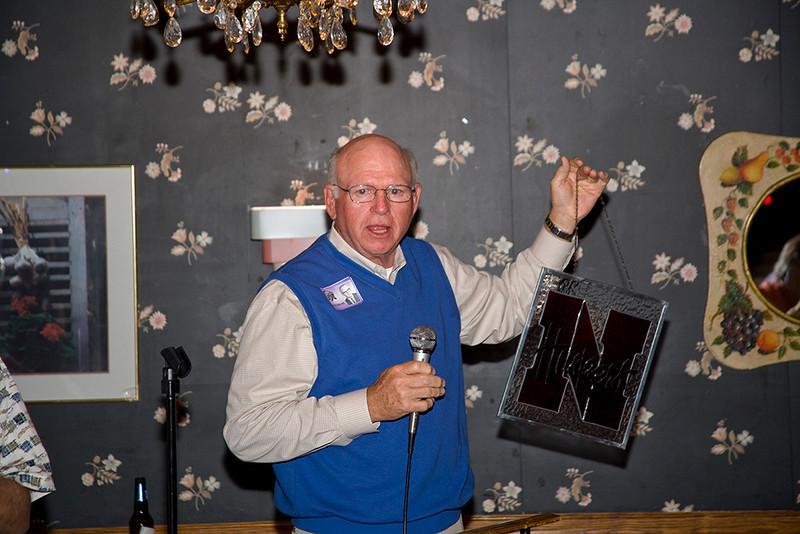 John Bennett holds the stained glass for auction.