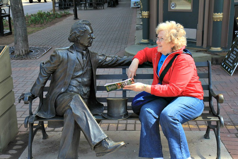 Linda talking with a local on a bench