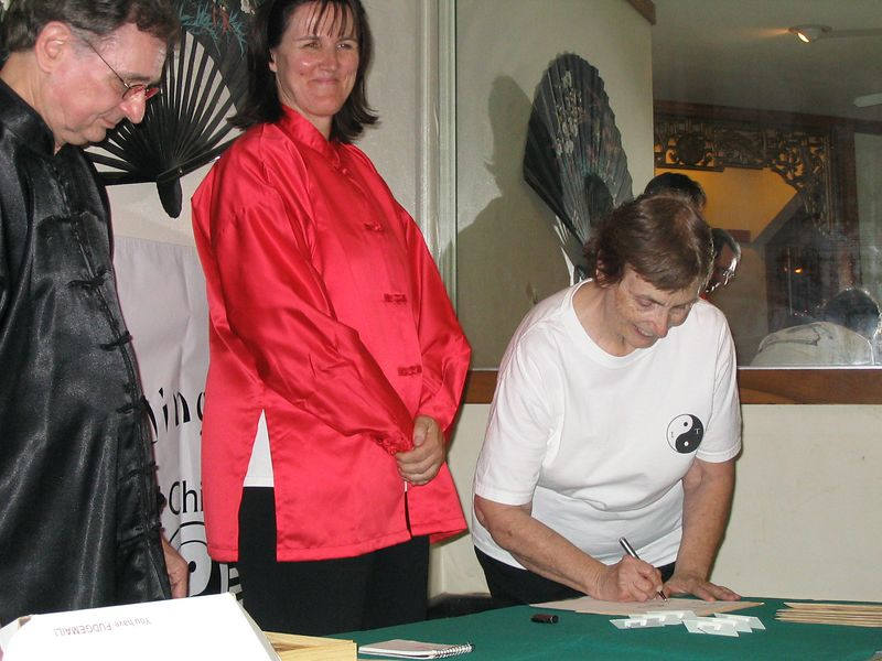 Certified Instructors Judith Forsyth and Phillip Szpiech look on as Barbara Hartin makes her second year commitment with the signing ceremony.  Oct. 18, 2003