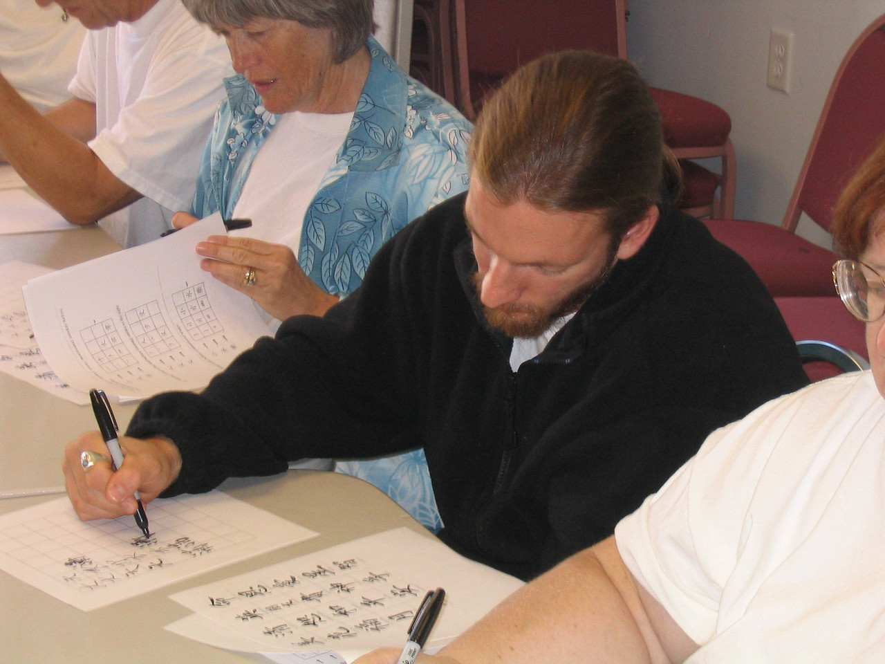 Bonnie Osborn (blue) and Nick Levinsky (black) practice writing their newly chosen Chinese character. Oct. 18, 03