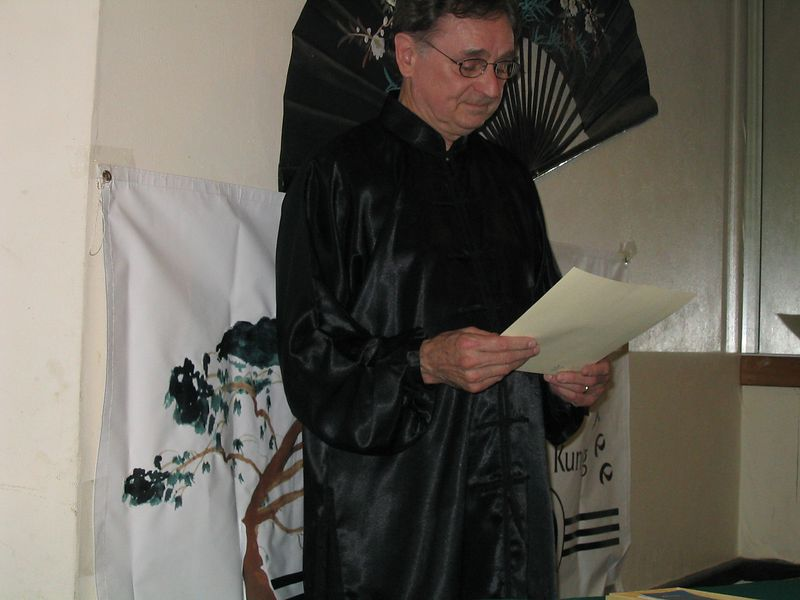 "Phillip Szpiech reads about a special gift to the students.  The gift was a small eraser shaped as a yin yang symbol.  Phillip reminded the new Assistant Instructors that they will have more personal contact with the students this year and that they cannot ""erase"" what they say.  He told them to speak with pure intent."