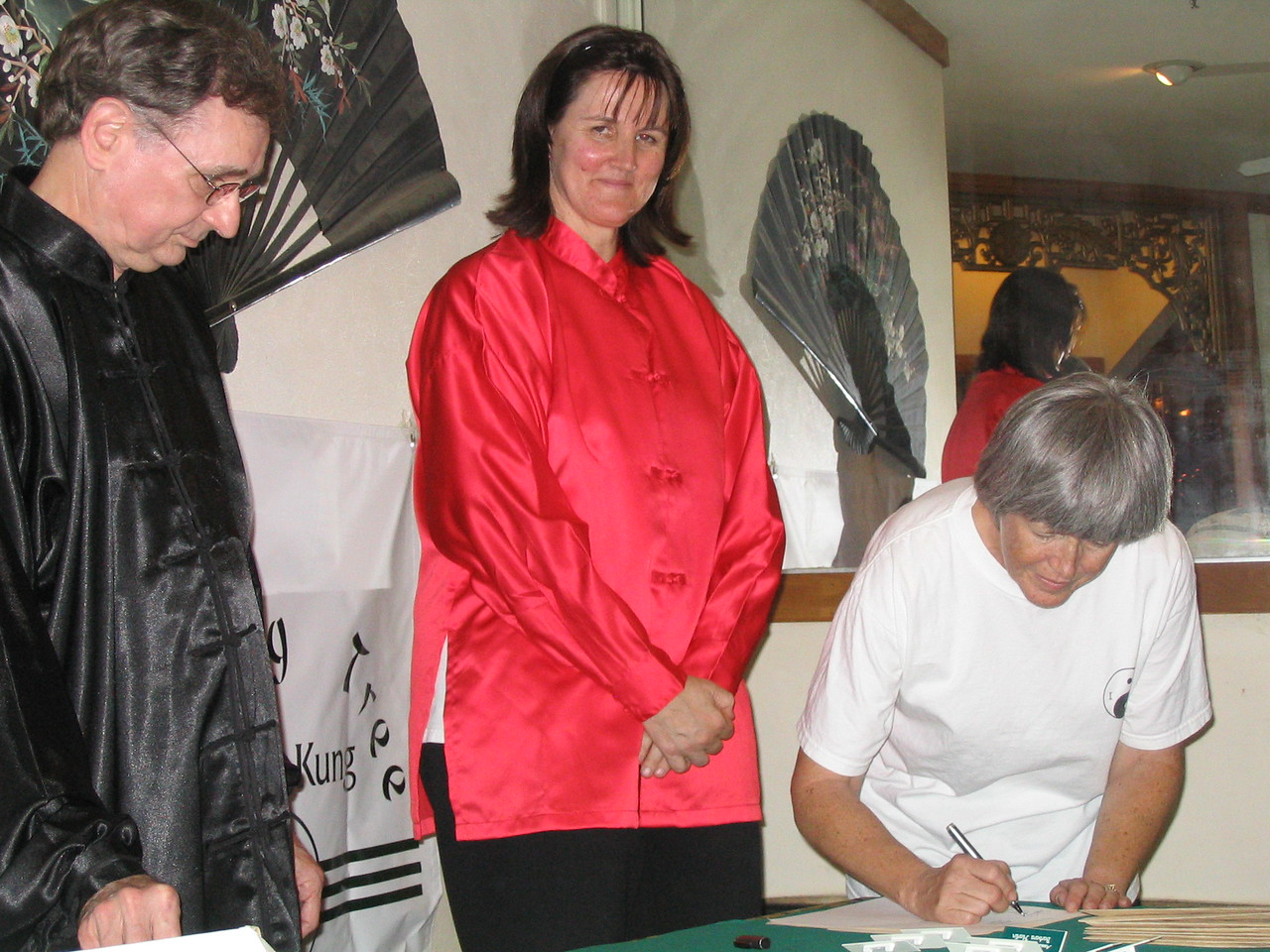Instructor and Founder of Bending Tree Tai Chi (red), Judith Forsyth smiles as Bonnie Osborn signs her Chinese symbol during her signing ceremony.  Instructor Phillip Szpiech waits to stamp her hand with her chosen symbol.