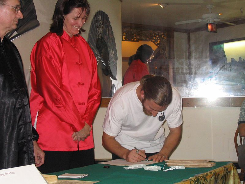 "The Signing Ceremony- Instructor Trainees are promoted to Assistant Instructor in a quiet ""signing and pinning"" ceremony.  Here, Phillip Szpiech (L) and Judith Forsyth (middle) witness Instructor Trainee Nick Levinsky sign on top of his Chinese symbol.  Judith signed on the bottom.  This represents the student's commitment to the program, and Bending Tree's commitment to the student.  Oct. 18, 2003"