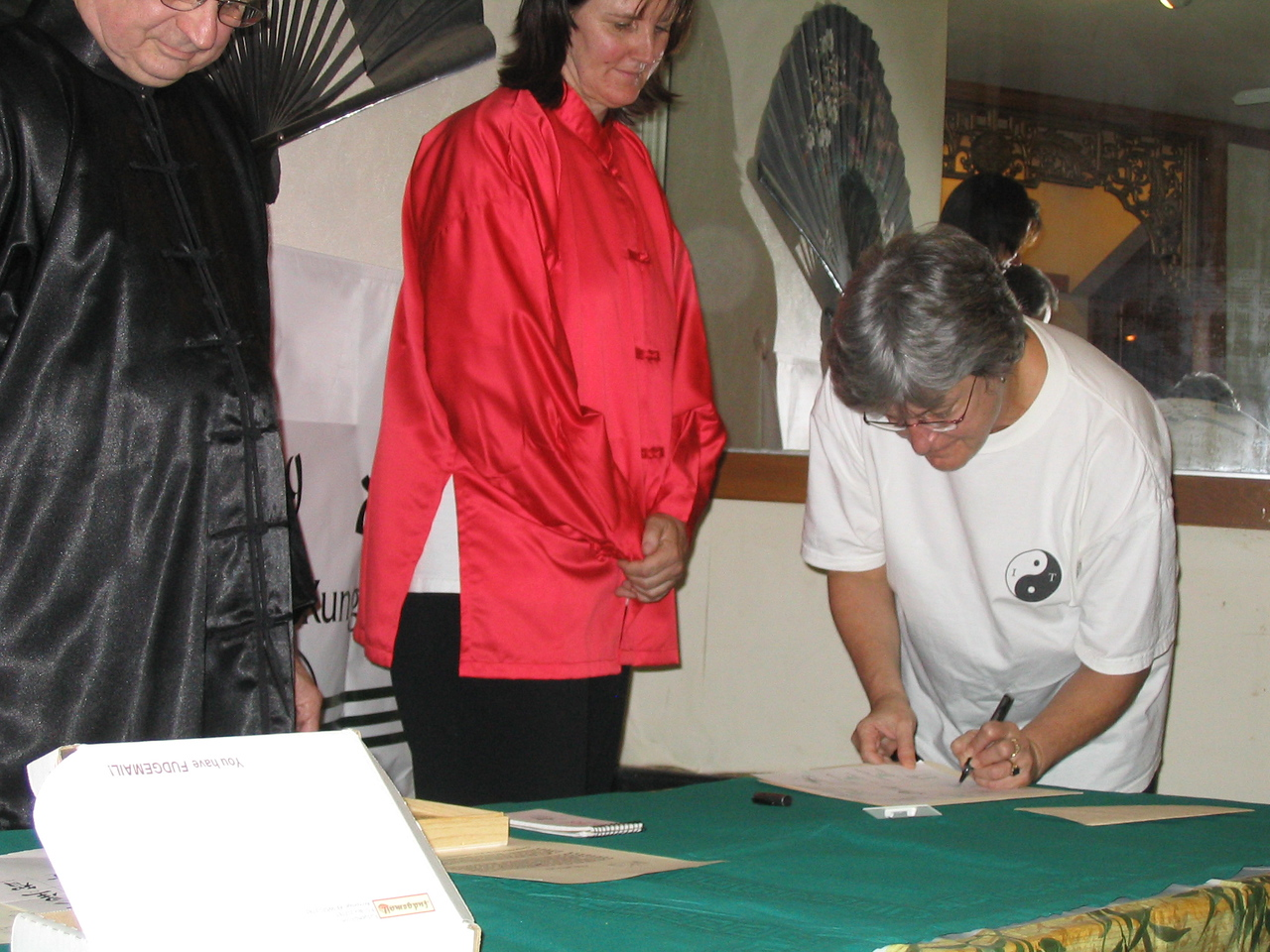 Pat Sullivan participates in the signing ceremony to demonstrate her commitment as Assistant Instructor for the second year of the Instructor Training Program with Bending Tree Tai Chi Kung.  Oct. 18, 2003