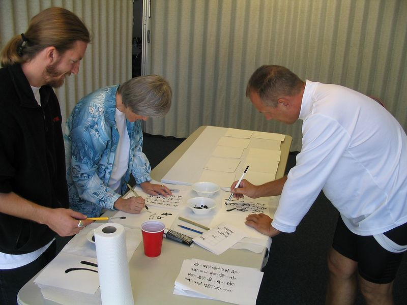 Assistant Instructor (and resident artist) helps Instructor Trainees Bonnie Osborn and Marty Kidder learn how to use the paint brush and black paint.  They are getting ready to paint their chosen symbol on a canvas.  Oct. 18, 2003, Instructor Training Session.