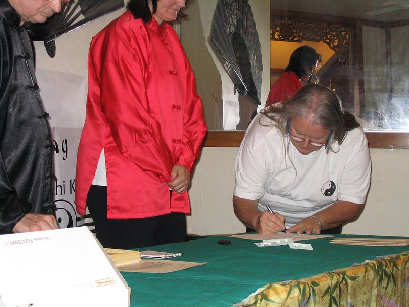 Liz Lipp signs her commitment to the second year program as Assistant Instructor while Instructors Judith Forsyth and Phillip Szpiech look on.  Oct. 18, 2003