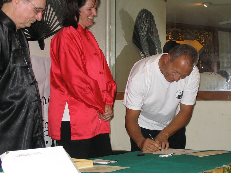 Instructors Judith Forsyth and Phillip Szpiech, watch as Marty Kidder signs his Chinese symbol as a demonstration of commitment to his Assistant Instructor position. Oct. 18, 2003
