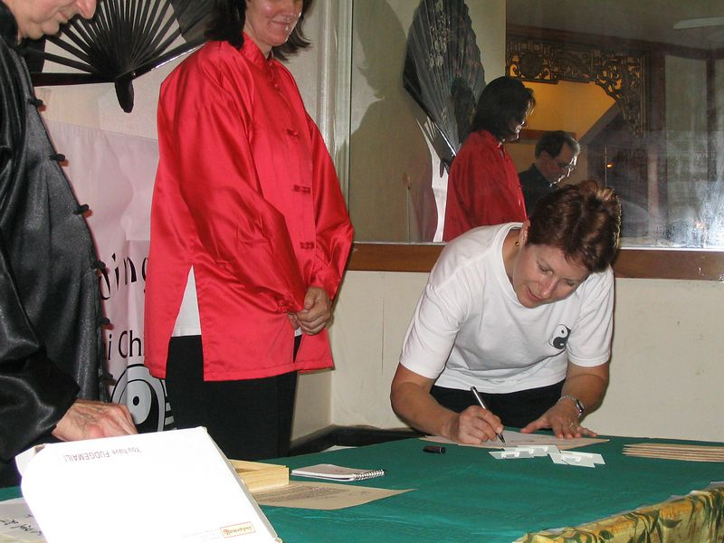 Janice Wells signs across her new Chinese symbol as commitment to her second year in the Instructor Training program.  Oct. 2003