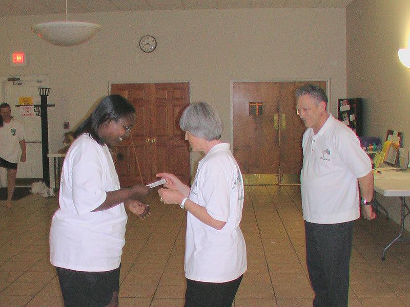Keona Evelyn received her graduation card from Bonnie Osborn as William Osborn looks on.  EEC 05/31/06 Longevity Tree.