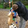 Ben rides a wooden playground pony