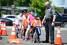 David LaChance — Bennington Banner<br /> Riders wait their turn for the Banner Game, aiming to deliver newspapers into milk crates, as Officer Cory Kingston watches.