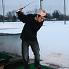 (Thursday March 13th 2014 - Royal Oak Golf Center, Royal Oak, MI) Berkley High's Curtis Carne takes a swing at practice at the Royal Oak golf center onto still snow covered driving range. Photo by: Brian B. Sevald