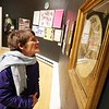 "BEN GARVER — THE BERKSHIRE EAGLE<br /> Felicity McClenachan looks at some needlework at the ""She Shapes History"" exhibit  at The Berkshire Museum, December 3, 2019."