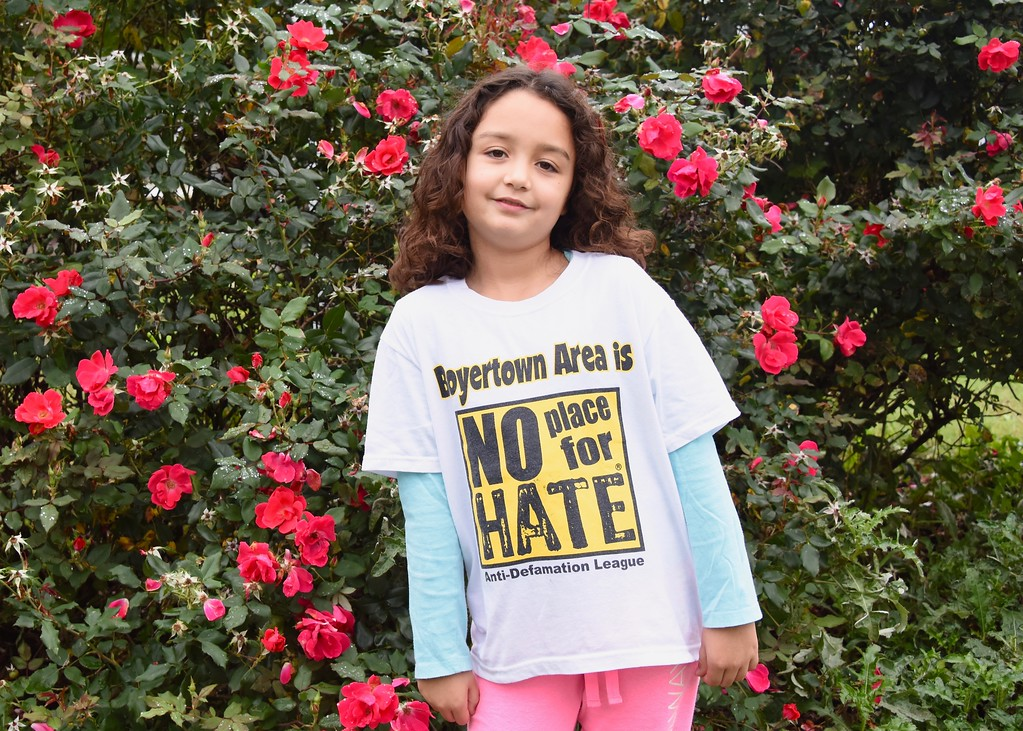 """. Unity Walker, 8-year-old Hana Lafond poses in her \""""No Place For Hate\"""" shirt."""