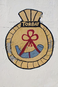 Crest of HMS Torbay at Dockyard, Bermuda. There have been five Royal Navy ships named HMS Torbay. The fifth (S90) is a Trafalgar class nuclear powered submarine launched in 1987 and still in active service (2012).