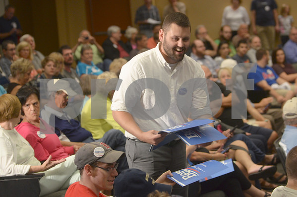 -Messenger photo by Jesse Major<br /> Evan Burger, advance staff for presidential hopeful Sen. Bernie Sanders, I-Vermont, passes out signs during the town hall meeting in Fort Dodge Thursday.