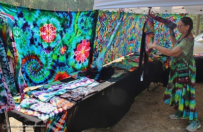 Sunlight sets tie-dye clothes aglow in the booth of Debs Kislingbury-Boivie Saturday at the 20th annual Berry Festival in Berry Creek. All the products up for sale had to be hand made under the festival rules. (Steve Schoonover -- Enterprise-Record)