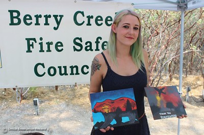 Misty McDivitt shows off a couple of paintings she made and was selling Saturday at the Berry Creek Berry Festival, with proceeds to go to local firefighters. (Steve Schoonover -- Enterprise-Record)